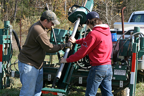 Members of the Big Creek Research and Extension Team work with a soil probe to extract a soil core for nutrient and physical analysis on a permitted manure application field. (U of Arkansas System Division of Agriculture photo).