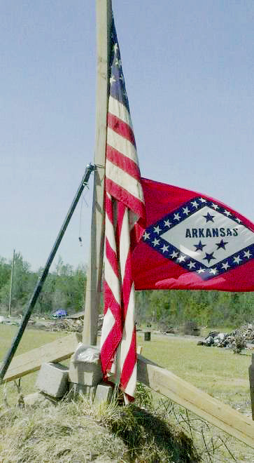 Two flags of America and Arkansas, battered but still waving near Vilonia.
