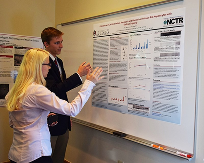 "Biomedical engineering student Alec Salminen presents his research on how, ""Crizotinib and Ceritinib Induce Apoptosis and Necrosis in Primary Rat Hepatocytes with Distinct Capacity"" to Professor Hanna Jensen."
