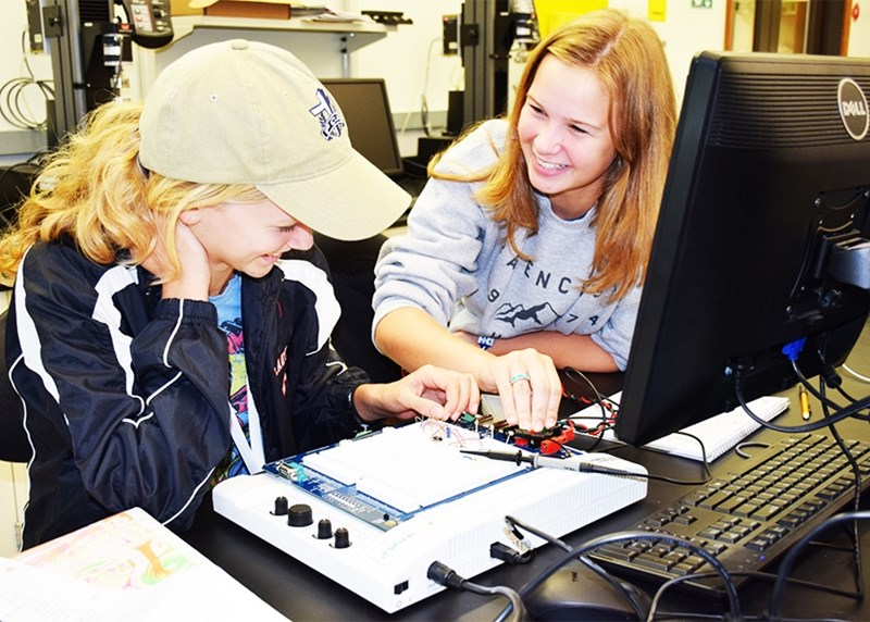 High school students Evelyn Smith and Ellie Toothaker collaborate on an EKG built from a breadboard.