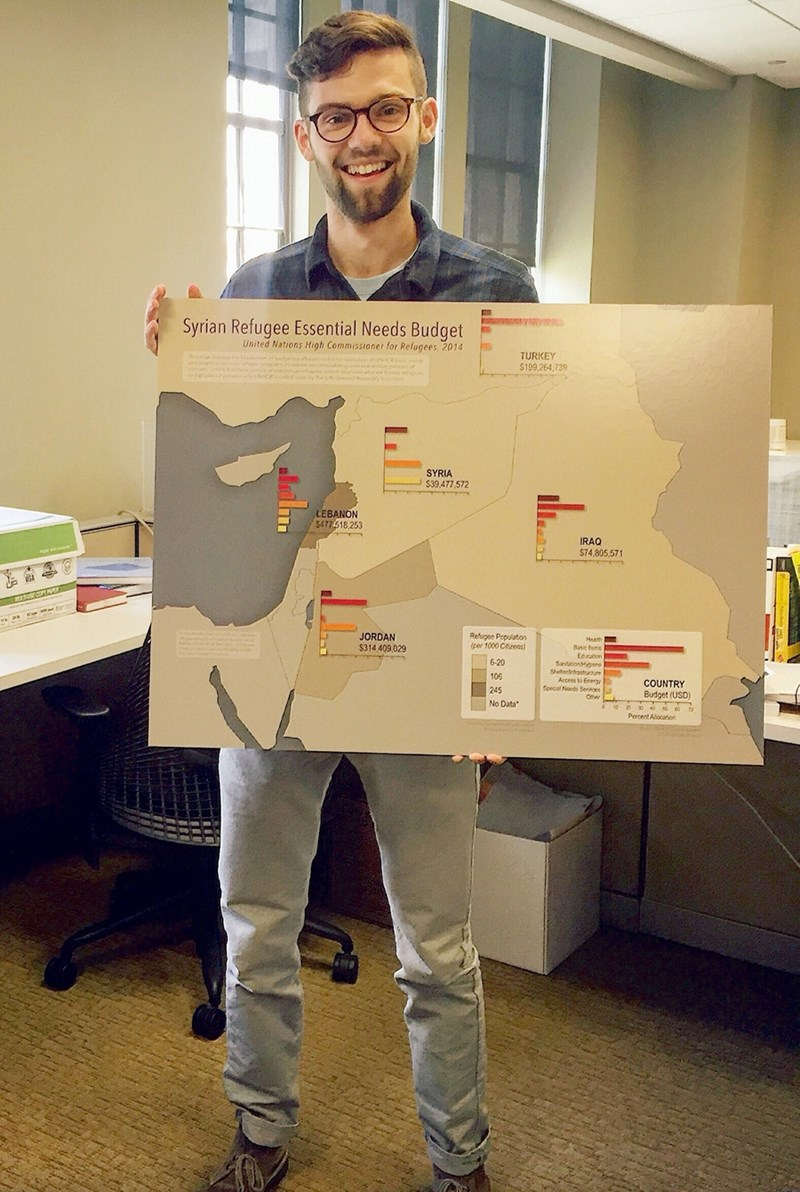 Bradley Wilson poses with a map outlining the Syrian refugee essential needs budget.