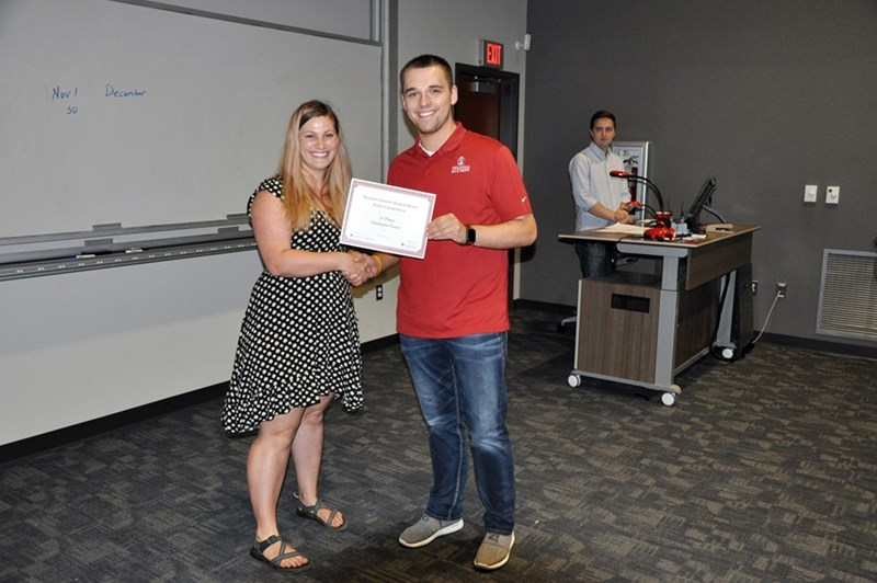 Dylan Cleary (left), a master's degree student in entomology, was named winner of the graduate division in the Bumpers College Research Poster Contest. Sam Harris, chair of the Honors Student Board, presents the award.