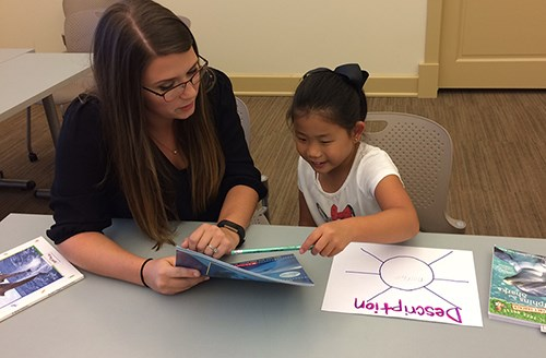 A University of Arkansas student works with a literacy camp participant last year.
