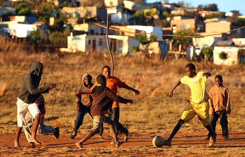 "African boys enjoy a pickup game of soccer. Todd Cleveland notes that ""virtually every great player from Africa started playing on a dirt pitch - the entry cost is negligible."""
