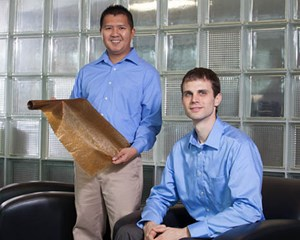 Nhiem Cao (left), president and CEO of cycleWood Solutions Inc., and company co-founder Kevin Oden pose with their film sample of a biodegradable plastic. Photo by Russell Cothren, University of Arkansas.