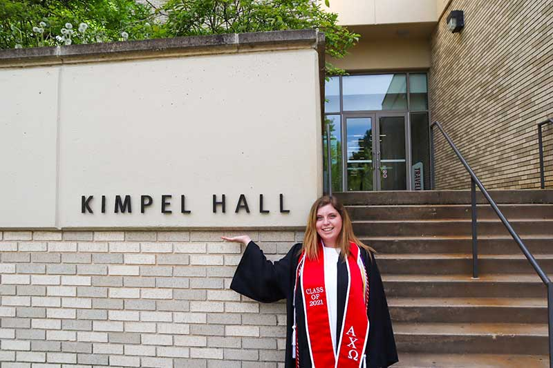 Alexis Campbell in her graduation regalia standing in front of Kimpel Hall