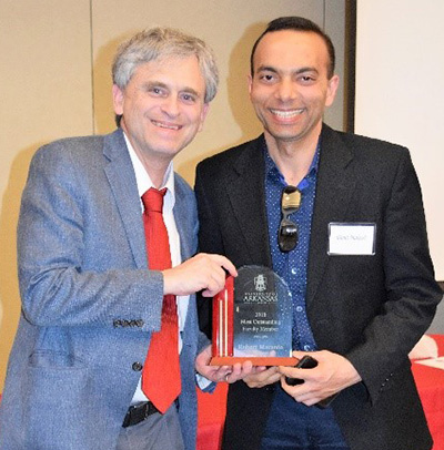 Robert Maranto accepting a faculty award from Dany Shakeel.