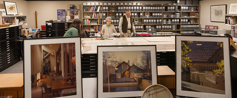 A photo of the architectural archives room at Mullins Library with Ellen Compton at center.