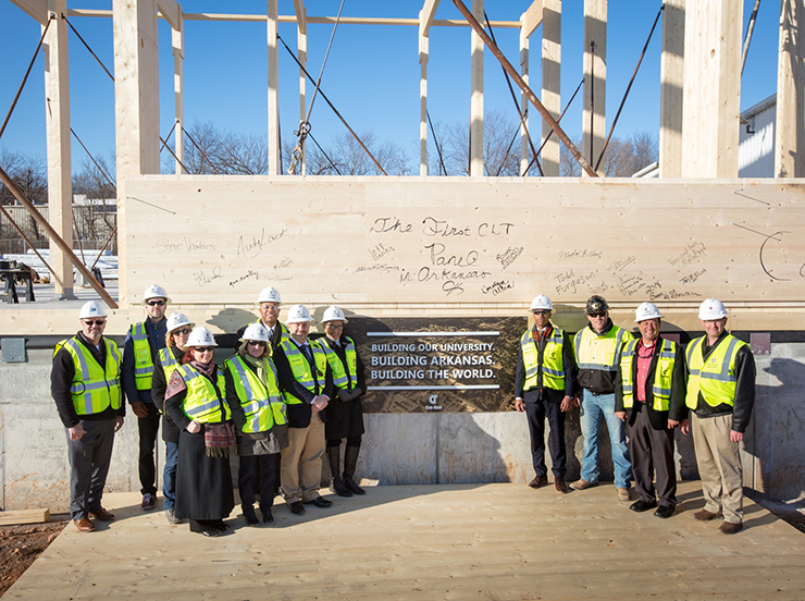 Participants pose for a photo at the beginning of construction of a new library storage building that uses cross-laminate wood as structural members.