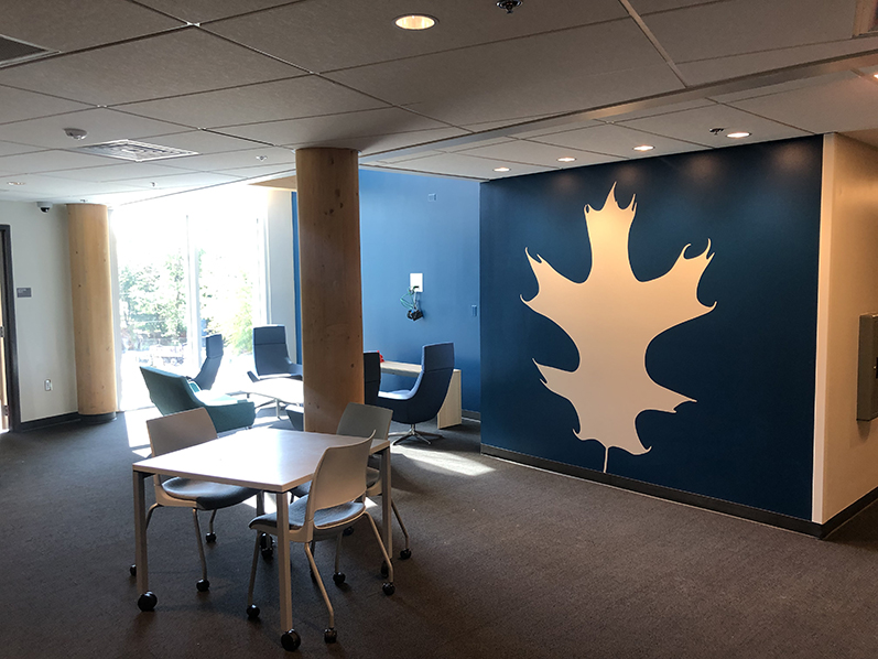 An interior common area on one of the residential floors of Adohi Hall includes a bright silhouette of an oak leaf on the wall.