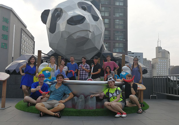 Students pose with a sculpture of a Great Panda.