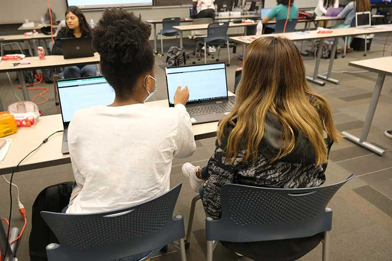 Two students train in machine learning on a computer