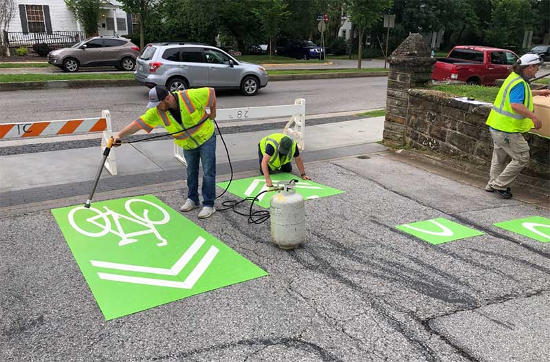 Workers install new bicycle directional signs at the entrance to Carnall Hall