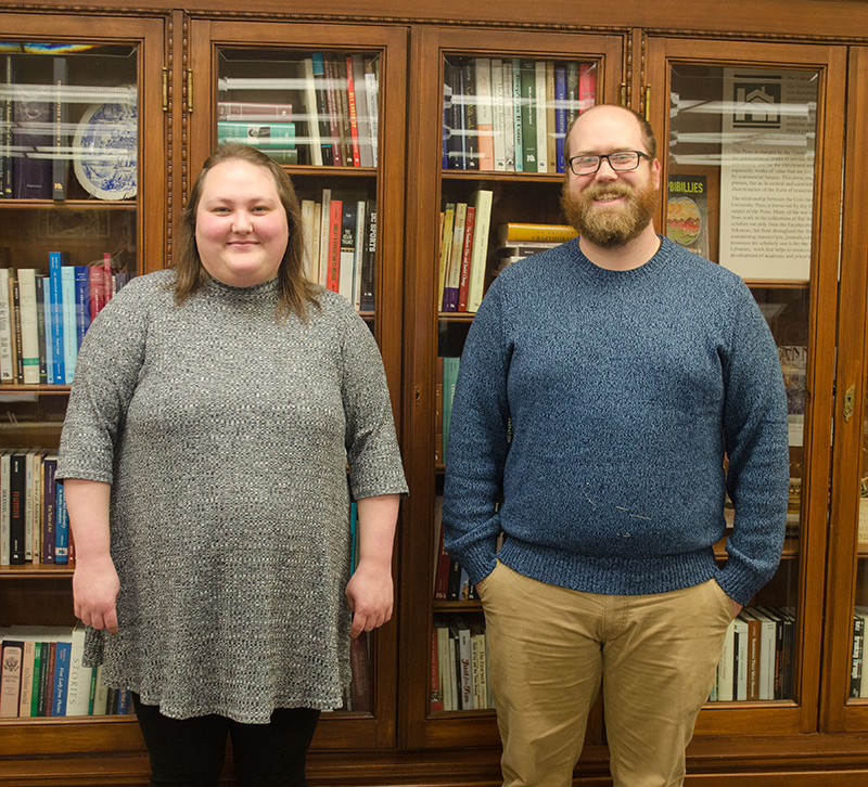 Photo of Megan York and Sam Owensby in Special Collections with bookcase behind them.