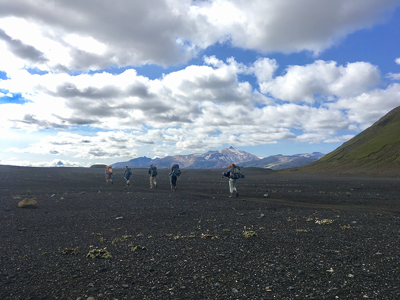 Trip participants hike into the black glacial desert between Alftavatn and Emstrur, Iceland.