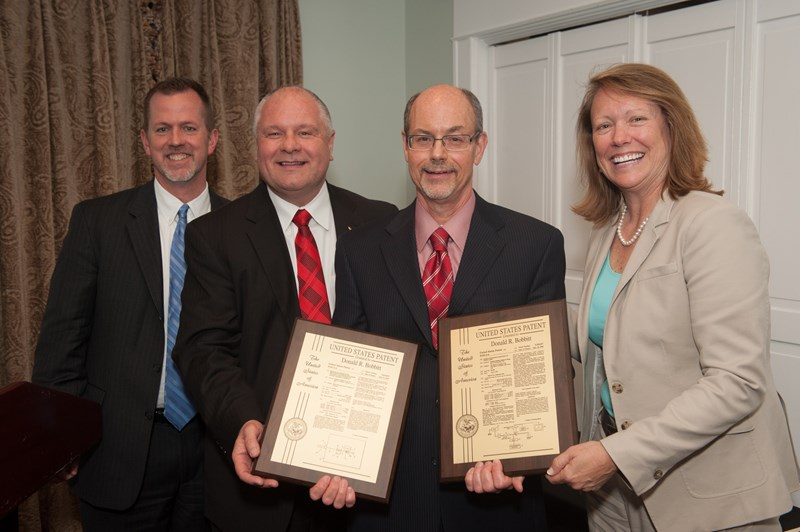 Donald R. Bobbitt (third from left), president of the University of Arkansas System, accepts plaques for his patents at the second annual Inventors' Appreciation Banquet. Presenting Bobbitt the plaques are Jeff Amerine (from left), director of Technology Ventures at the U of A; Jim Rankin, vice provost for research and economic development; and Sharon Gaber, provost and vice chancellor for academic affairs.