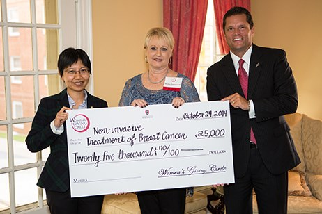 Jingyi Chen, an assistant professor of chemistry and biochemistry in Fulbright College, accepts a check for $25,000 from Women's Giving Circle president Martha Haguewood and Associate Vice Chancellor for Development Mark Power.