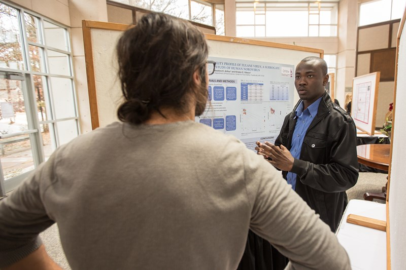 Sabastine Arthur, a master's student in cell and molecular biology, explains his research prior to Tuesday's ceremony honoring winners in the University of Arkansas' annual graduate student poster competition. Arthur finished first in the food science category. Photo by Matt Reynolds, University of Arkansas.