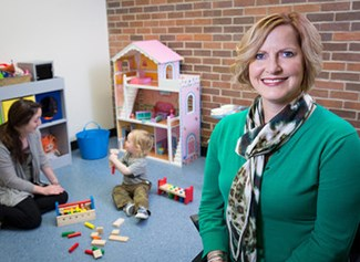 Kristi Perryman directs the new Office of Play Therapy Research and Training at the University of Arkansas. Behind her, Bonni Behrend, a counselor education doctoral student, works with 2-year-old James.