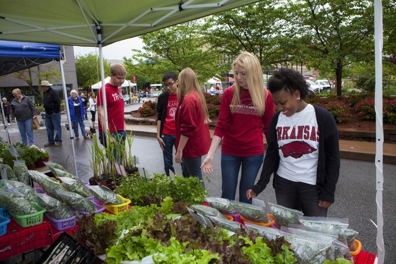 University of Arkansas students shop at the Fayetteville Farmers Market. A new grant will allow customers enrolled in two nutrition programs to double their purchasing power at regional farmers' markets.