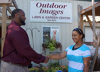 Demarcus Wiggins, PROMISE case manager for Benton County, congratulates Cyndi Saucier on a job well done. Cyndi worked at Outdoor Images Lawn & Garden Center in Siloam Springs and is a sophomore at Siloam Springs High School.