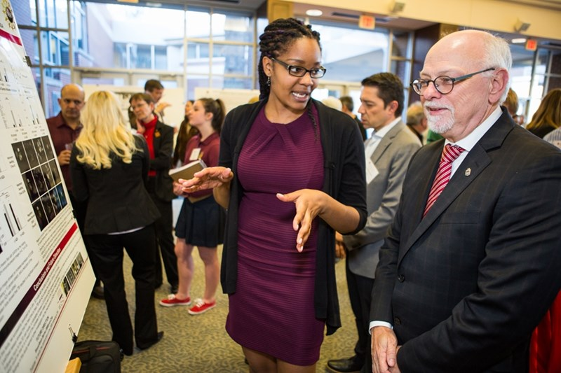 Nasya Sturdivant, a biomedical engineering doctoral student, explains her research to Chancellor Joe Steinmetz at the neuroscience research showcase.