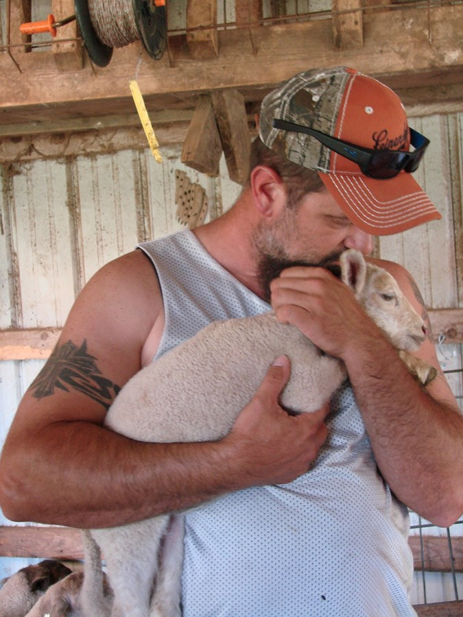 Veteran farmer, Robert Cooley of Texas, snuggles a baby lamb at Maple Gorge Farm last week during Armed to Farm workshop when learning about livestock care and handling.
