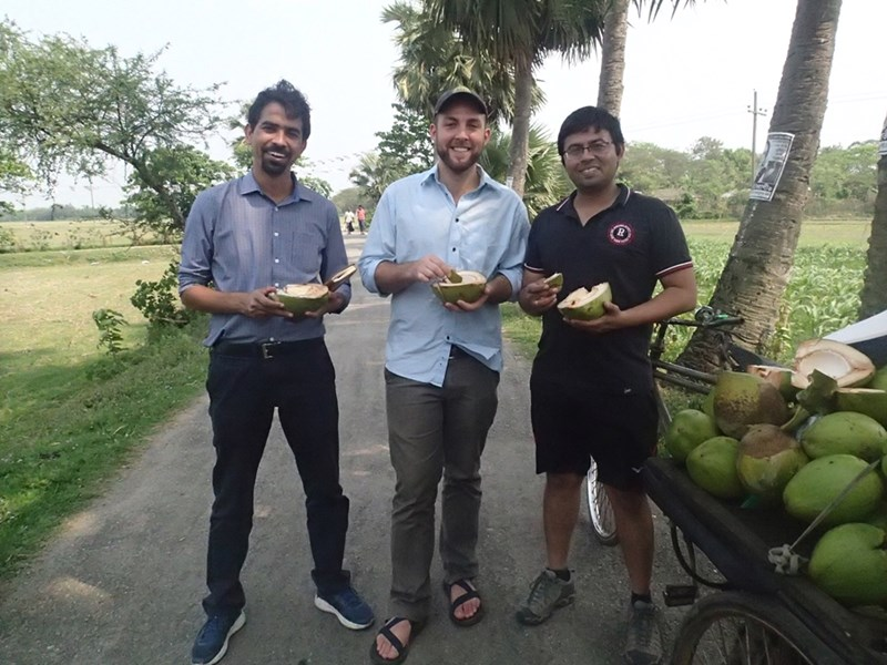 Aaron Shew (middle) and his research colleagues take a break from their work to enjoy a coconut