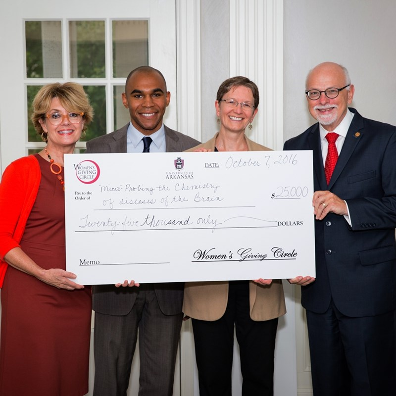 Associate Director of Development Charles Gaines and Professor Ingrid Fritsch (center) from the J. William Fulbright College of Arts and Sciences accept a check from Women's Giving Circle President Melissa McIlroy Hawkins (left) and Chancellor Joe Steinmetz (right). Fritsch's proposal received $25,000 at the circle's 14th annual grant awards ceremony.