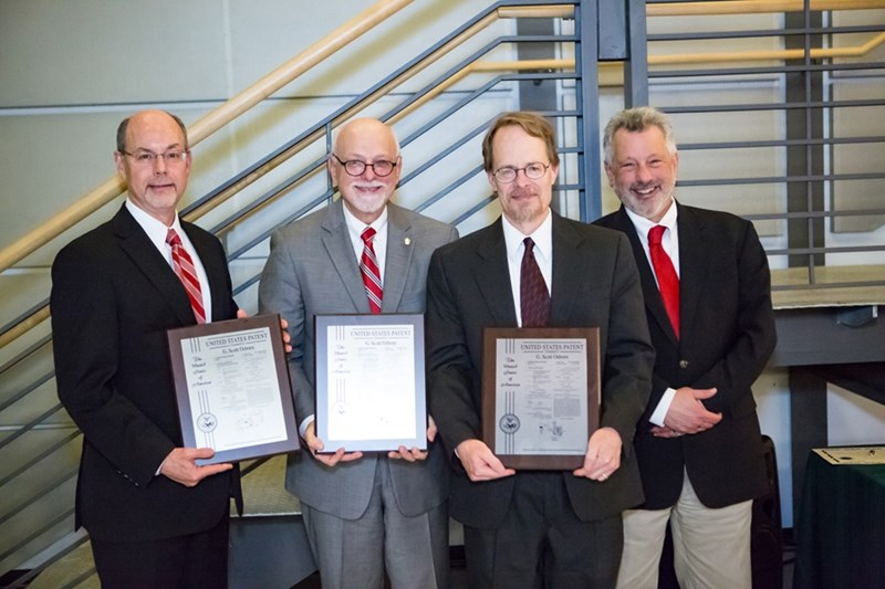 University of Arkansas System President Donald R. Bobbitt (far left), Chancellor Joe Steinmetz (center left) and Jim Coleman, provost and executive vice chancellor (far right) with patent-plaque recipient Scott Osborn, associate professor of biological and agricultural engineering.