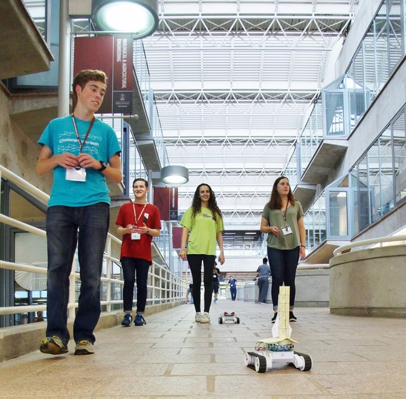 High school students Ben Tyrrell, Ben Anderson, Ruth Glauber, and Elizabeth Brice test their autonomous robots on the Bell Engineering ramp.