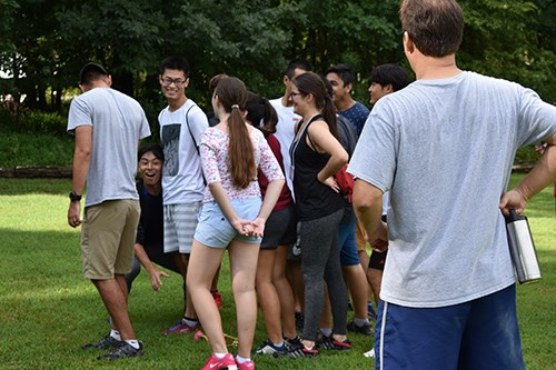 International students try to surreptitiously grab a rubber chicken from the ground during a game of Sneak Attack.