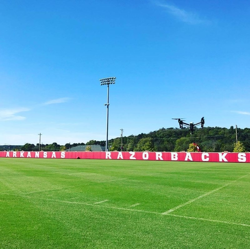 An unmanned aircraft system, or drone, flies over the Razorback's practice field.