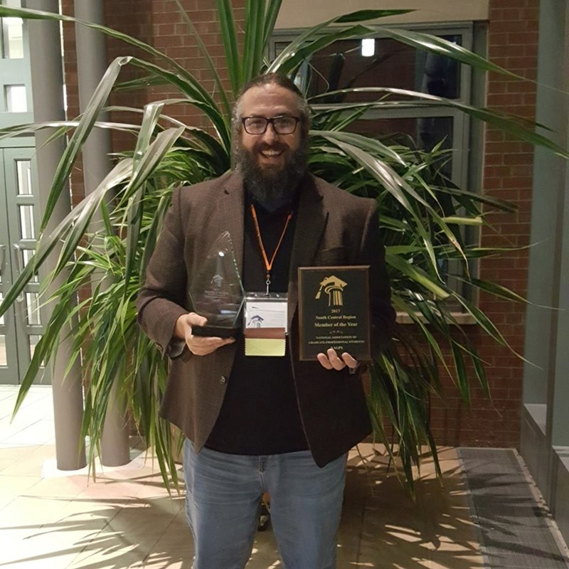 Arley Ward, speaker of the Graduate Student Congress, is pictured with the Regional and National Member of the Year Awards won by the organization at Syracuse University last week.