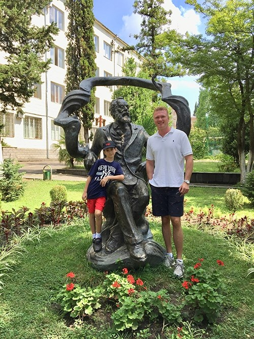 John Pijanowski and his 8-year-old son, Jack, who will join him in Kutaisi, are pictured on the campus of Akaki Tsereteli State University with a statue of the university's namesake.