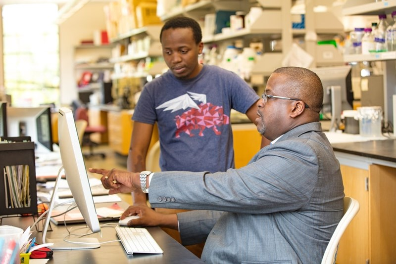 Paul Adams, associate professor, has served as research mentor for more than 70 students in the past 10 years, and will lead the Path to Graduation Program. Here, he confers with Djamali Muhoza, a doctoral student in the cellular and molecular biology program.