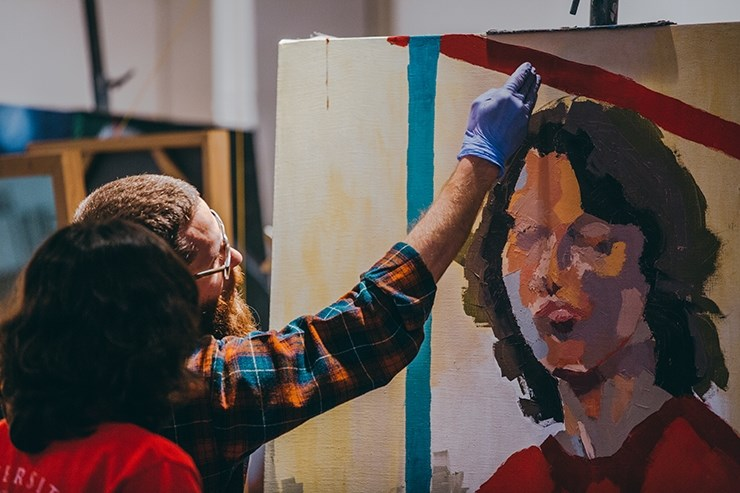 Visiting assistant professor David Andree gives a student feedback during a painting class at the University of Arkansas School of Art.