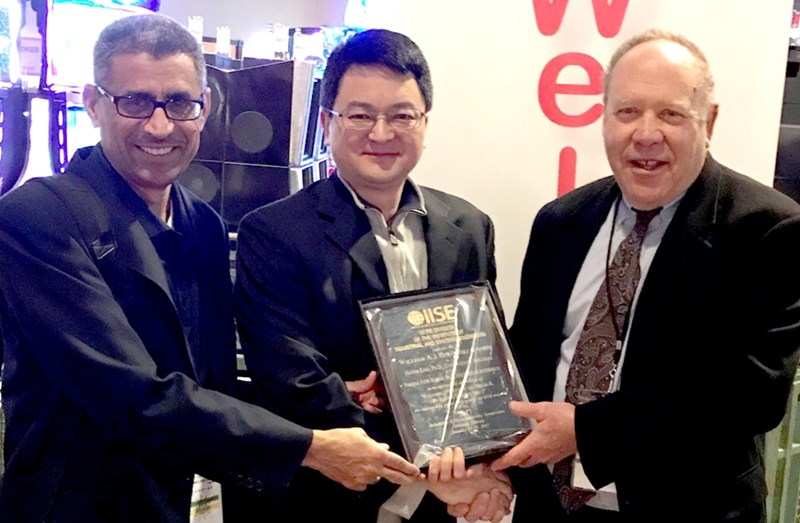 Dr. Haitao Liao, center, receives an award for his research at the Reliability and Maintainability Symposium.