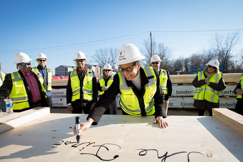 Carolyn Henderson Allen, dean of Libraries, signs the first cross-laminated timber panel installed in Arkansas.