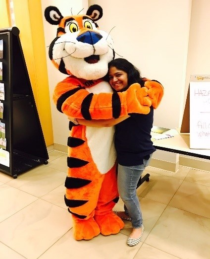 "Shilpa Samant, a Bumpers College doctoral student in food science, gets a hug from ""Tony"" the Tiger, the mascot for Kellogg's Frosted Flakes. Samant was named Kellogg's 2017 Outstanding Intern."