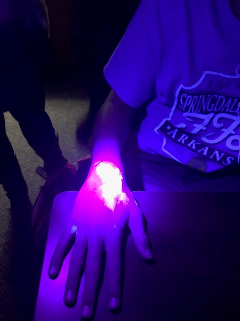 An ultraviolet light and Glo Germ powder was used to illustrate how quickly germs can be spread during a food science outreach experiment at Har-Ber High School.