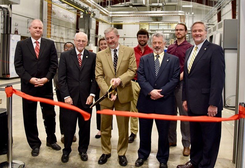 NCREPT Director Alan Mantooth cuts the ribbon celebrating the center's expansion. Front row from left are: Arkansas Senate Majority Leader Jim Hendren, Chancellor Joseph Steinmetz, Dr. Alan Mantooth, Provost Jim Coleman and College of Engineering Dean John English. Back row: Student researchers Janviere Umuhoza, Andrea Wallace, Daniel Schwartz andJoe Moquin.