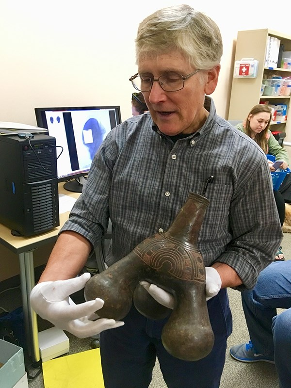 "George Sabo, director of the Arkansas Archeological Survey, discusses features of a 500-year-old Caddo ""tripod bottle."""