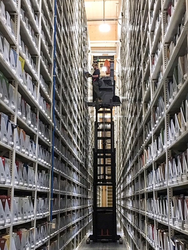 A worker retrieves a book from the Library Storage Facility