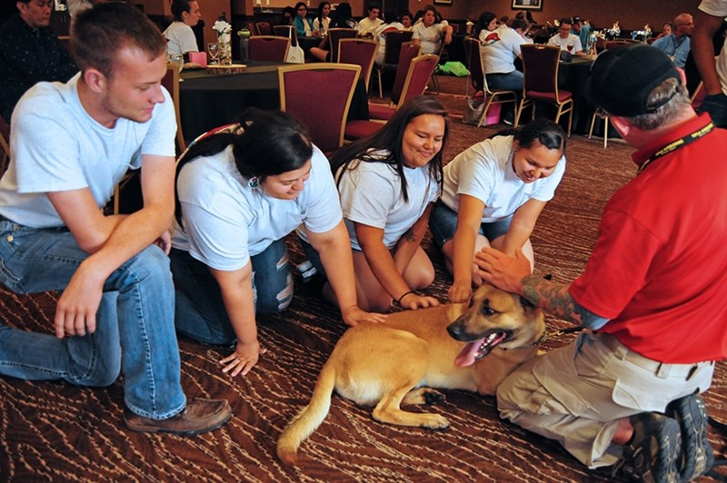 Native Youth in Food and Agriculture Leadership Summit students Zach Ilbery (Cherokee), Mackenize Martinez (Choctaw-Apache), Lauren Thompson (Cheyenne River Sioux), and Kiana Haskell (Fort Belknap) learn about the dog training operation at the Quapaw Tribe.