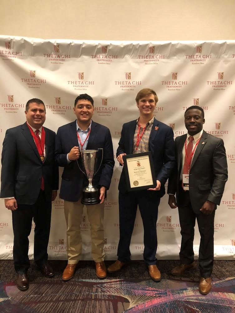 Executive Director Mike Mayer (far left) and Field Staff Member Kobe Ladans awarding brothers Aaron Banuelos (center left) and Jared Pinkerton (right) the Standford Trophy for Scholastic Achievement.