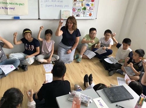 Jennifer Wiggins, a fifth-grade teacher in Springdale, works with children during a recent trip to China