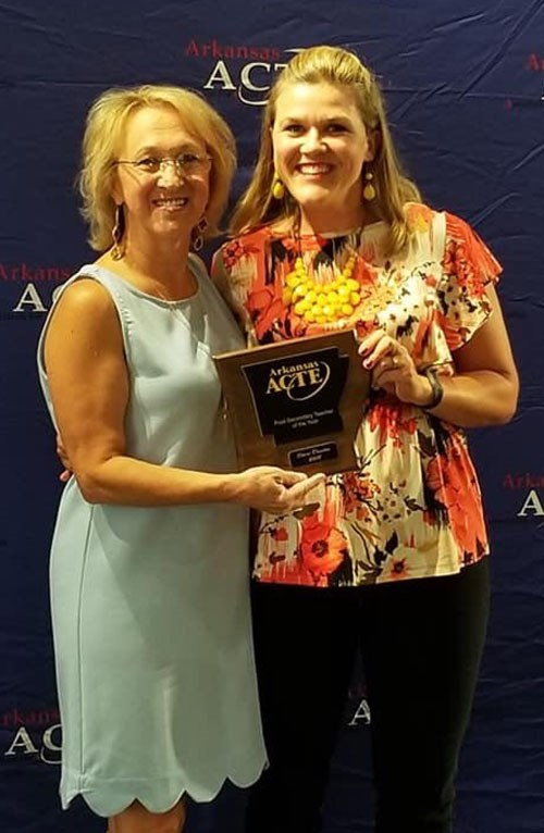 Sheri Deaton, right, receives one of her Teacher of the Year awards from Starlinda Sanders, president of the Arkansas Association for Career and Technical Education.