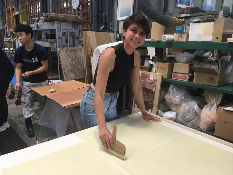 Honors College Fellow Olivia Fredricks flattens paper at the Awagami paper factory in Tokushima, Japan.