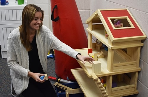 Ellen Bennett puts away toys used in play therapy during her internship at Turnbow Elementary School in Springdale.